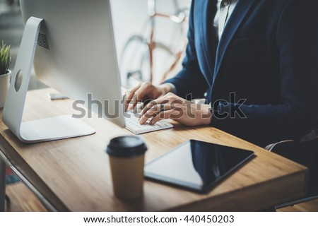 Professional businessman using modern computer while working at his office, digital tablet and coffee on wooden table, male lawyer working on technology at vintage loft, retro bike in the background