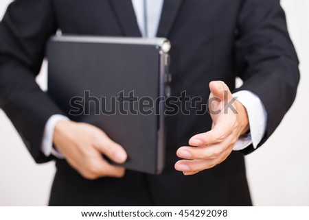 Professional businessman with laptop offering to shake the hand ready to seal a deal or cooperate,isolated