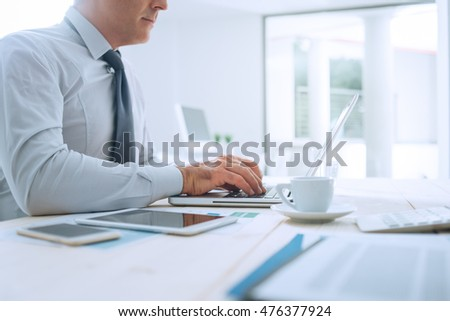 Professional businessman working at office desk and typing on a laptop, unrecognizable person