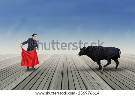 Professional businessperson using a red cloth to fight with a bull outdoors - stock photo