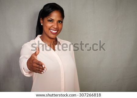 Professional businesswoman giving a hand shake while smiling at the camera - copy space - stock photo