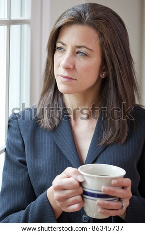 Professional businesswoman holding coffee cup looking thoughtful - stock photo