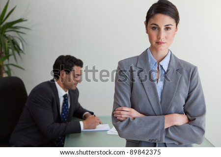 Professional businesswoman posing while her colleague is working in an office - stock photo