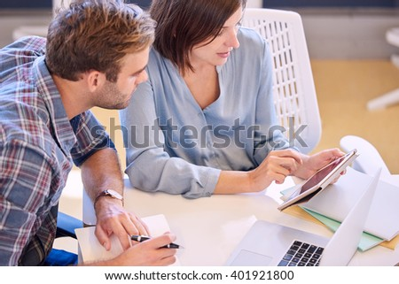 Professional businesswoman showing her male partner financial figures on tablet