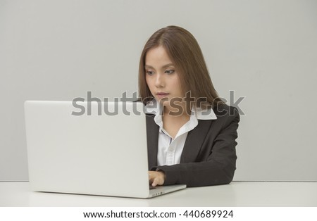 professional businesswoman sitting in front of laptop at her desk in an office while looking at laptop. - stock photo