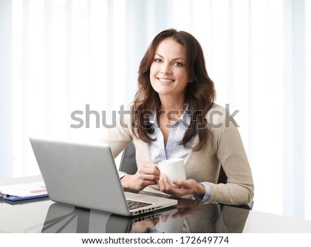 Professional businesswoman working on laptop in her office. - stock photo