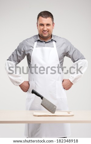 professional butcher smiling behind table. man standing with arms a-kimbo and in sleeves - stock photo
