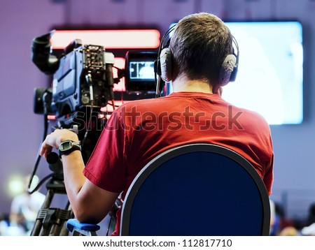 Professional cameraman with headphones with HD camcorder in live television - stock photo