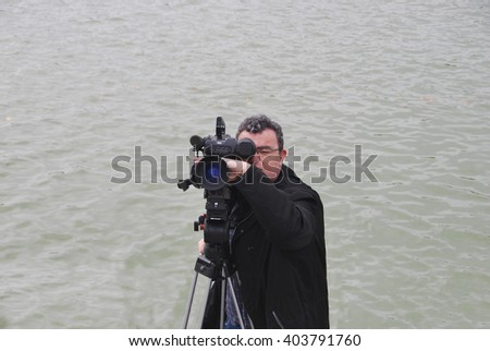 Professional cameraman with video camera in shooting process. Digital media - stock photo