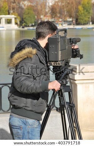 Professional cameraman with video camera in shooting process. Digital media recording - stock photo