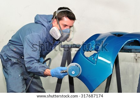 Professional car body repair, Painting blue bumper. - stock photo