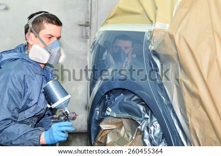 Professional car body repair, Painting side panel. - stock photo