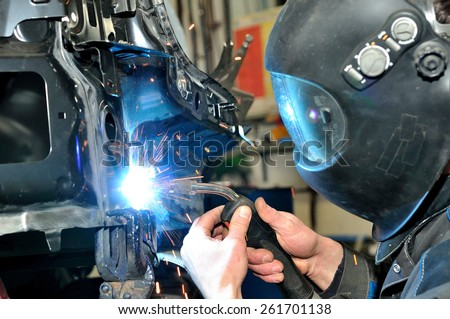 Professional car body repair, welding panels. - stock photo