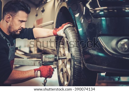 Professional car mechanic changing car wheel in auto repair service. - stock photo
