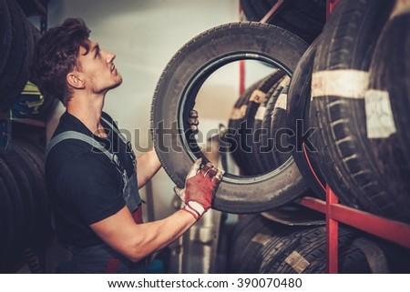 Professional car  mechanic choosing new tire in auto repair service. - stock photo