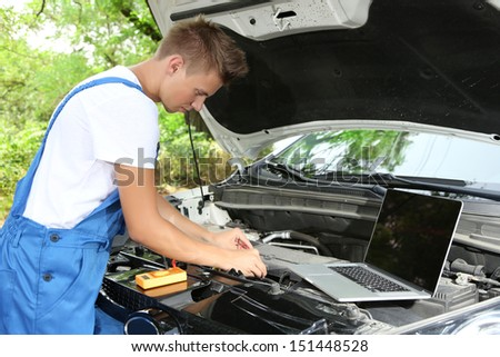 Professional car mechanic working in auto repair service - stock photo
