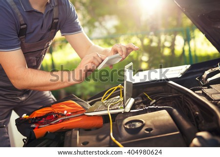 Professional car mechanic working in auto repair service, photographing damage on the car - stock photo