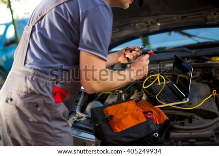 Professional car mechanic working in auto repair service, using laptop