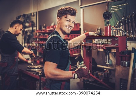 Professional car mechanic working with hydraulic press in auto repair service. - stock photo