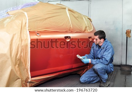 Professional car painter inspecting his work. - stock photo