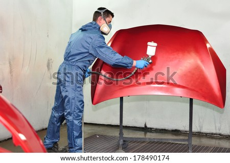 Professional car painter, painting red bonnet. - stock photo