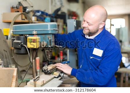 Professional carpenter using a boring mill to drill a hole in a piece of wood - stock photo