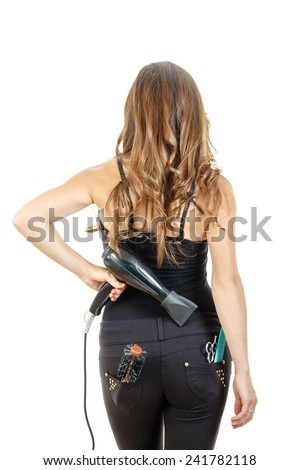 Professional caucasian brunette female hairdresser posing from behind holding hairdryer with brush and comb in back pocket, isolated on white backgropund.She has beautiful, long and healthy brown hair - stock photo