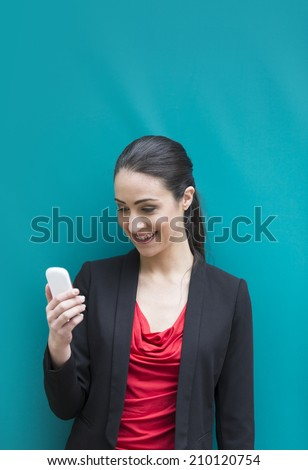 Professional Caucasian businesswoman leaning against a blue wall using a Cell Phone. Cheerful woman talking on smartphone. - stock photo