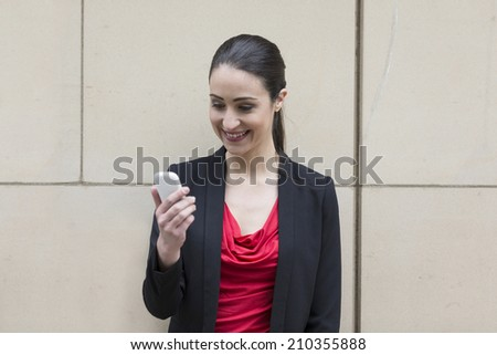 Professional Caucasian businesswoman leaning against a wall using a Cell Phone. Cheerful woman talking on smartphone. - stock photo