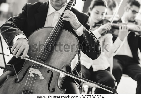 Professional cello player performing with other musicians, classical music symphony orchestra, unrecognizable person - stock photo