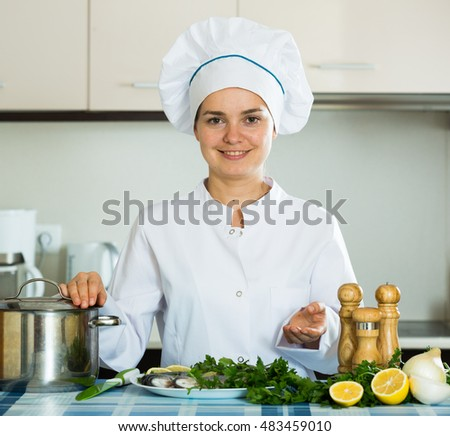 Professional chef cooking fresh mackerel at kitchen table