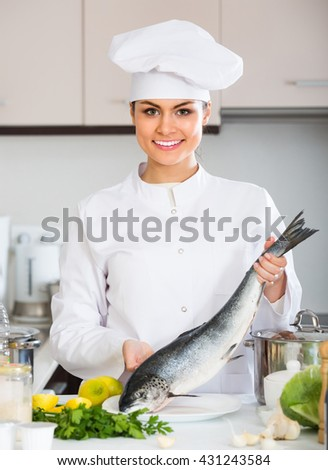 Professional chef cooking rainbow trout in commercial kitchen