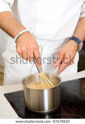 professional chef hands with kitchen utensils whisk and pan