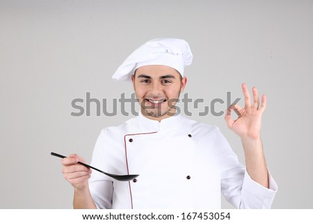Professional chef in white uniform and hat, on gray background - stock photo