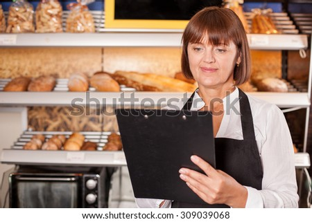 Professional chef is standing near shelves of pastry. The woman is holding a folder of recipe and reading it with concentration. She is smiling happily. Copy space in left side - stock photo