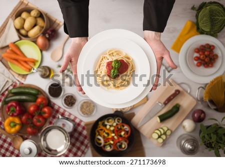 Professional chef's hands cooking pasta on a wooden worktop with vegetables, food ingredients and utensils, top view - stock photo