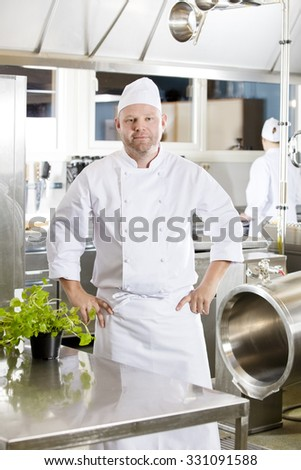 Professional chef standing in large kitchen - stock photo