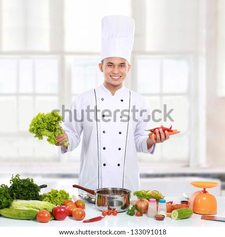 Professional chef with fresh ingredient ready to cook some food - stock photo