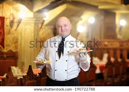 professional chef with prepared food on plates in commercial  - stock photo