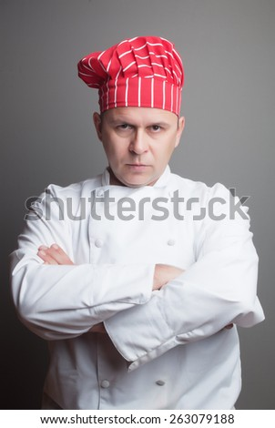 Professional chef with red hat, studio shot over gray background - stock photo