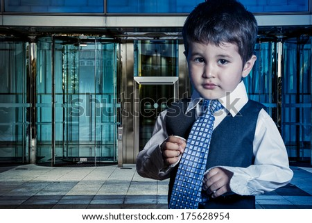 Professional child dressed businessman with hands in his tie and skyscrapers in the background - stock photo