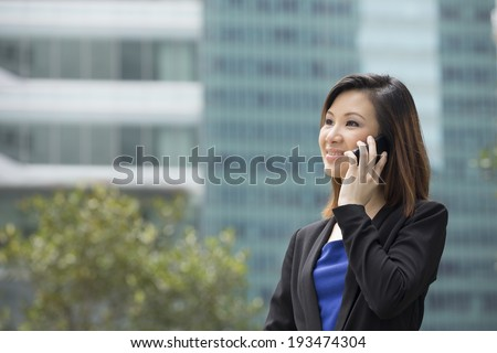 Professional Chinese businesswoman outside in modern city using a Cell Phone. Asian or Chinese woman talking on smartphone.  - stock photo