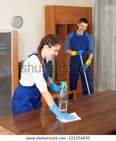 Professional cleaners working at living room - stock photo