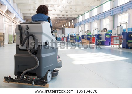 Professional Cleaning Factory Floor with Washing Vacuum Cleaner - stock photo