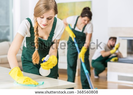 Professional cleaning service in uniforms during work - stock photo