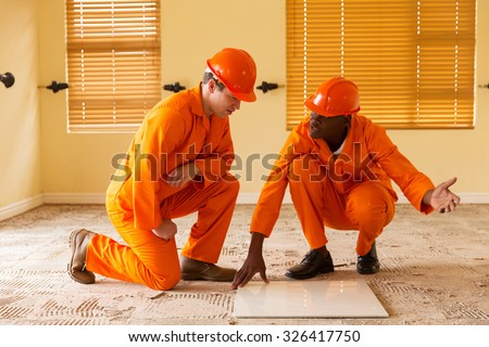 professional construction co-workers discussing floor tiles - stock photo