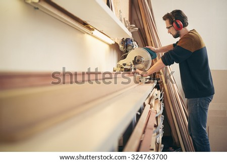 Professional craftsman at work in a framing workshop using a saw tool to work with wood - stock photo