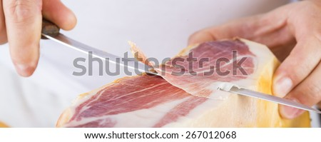 Professional cutter carving  slices from a whole bone-in serrano ham - stock photo