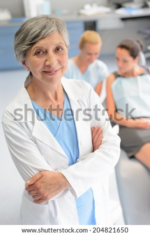 Professional dentist surgeon woman assistant with patient at dental clinic - stock photo