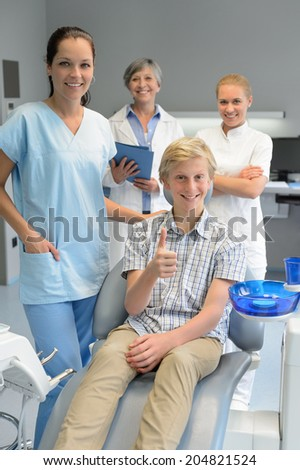 Professional dentist team with teenager boy patient thumb-up dental surgery - stock photo